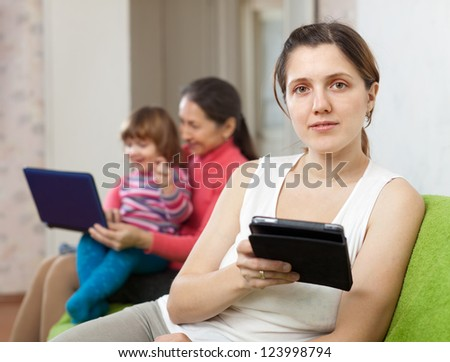 women of three generations sits on the sofa with electronic devices