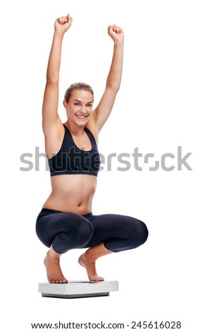 Women on scale cheering for achieving her weight loss goal isolated on white background