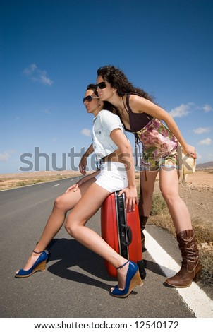 women on the road waiting for a car under the blue sky