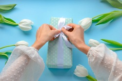 Women opens gif. Packing gift present.mother  and women day.Blue flowering background.