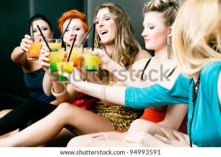 Women or models in club or disco drinking cocktails having fun