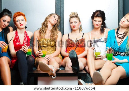 Women or models in club or disco drinking cocktails having no fun as the party is boring