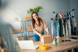 Women, owener of small business packing product in boxes, preparing it for delivery. Women packing package with her products that she selling online. Small business owener