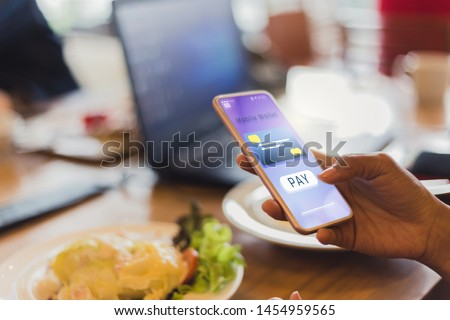 Women pay for food Using credit cards through mobile phones in restaurants, future IOT and technology concepts