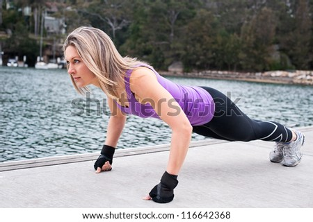 Women planking outdoors close to the water