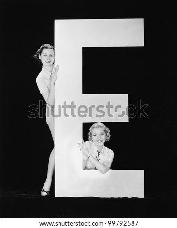 Women posing with huge letter E