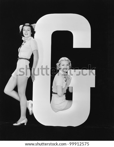 Women posing with huge letter G