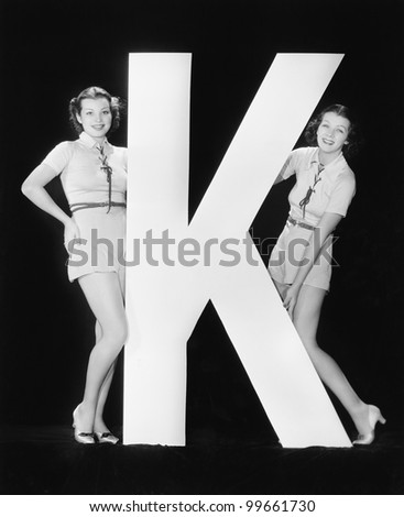 Women posing with huge letter K