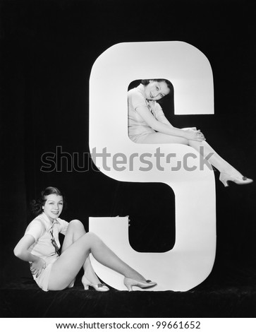 Women posing with huge letter S