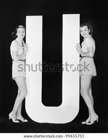 Women posing with huge letter U