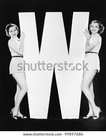 Women posing with huge letter W