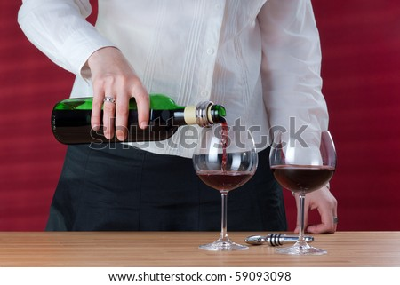 Women pouring red wine into wineglass. Next to her stay two wineglasses and carafe. Red background behind her with sun beams and shades.