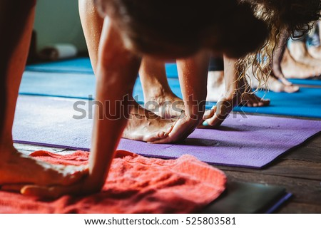Women practicing yoga and meditation in retreat studio class during Bali vacation recreation