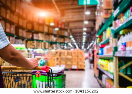 Women pushing shopping trolly in the supermarket aisles, shopping concept