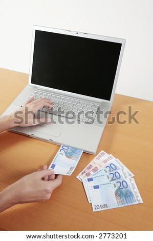 women puting euro bills inside the the cd-rom opening of a laptop computer