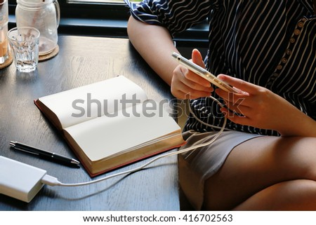 women reading book and use phone, using mobile smart phone, Internet of things lifestyle with wireless communication and internet with smartphone.