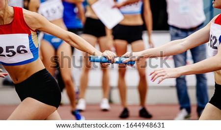 women relay team passing of baton running 4x400 meters  Foto d'archivio ©