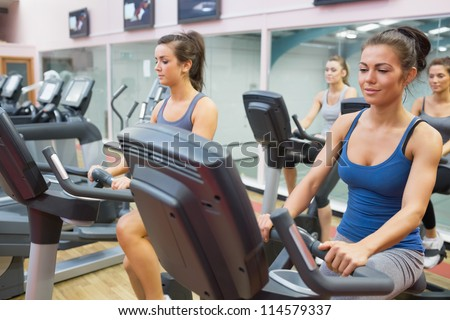 Women riding on  exercise bikes in spinning class in gym