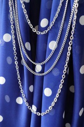 Women's accessories: blue chiffon scarf in white peas and silver chain close-up