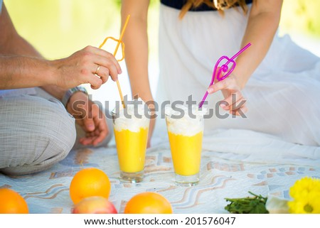 Women\'s and men\'s hands with wedding rings. Picnic in the nature. The glasses of orange juice and whipped cream. Summer vacation concept.