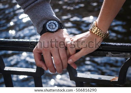 women's and men's watches. man's hand holding a female.