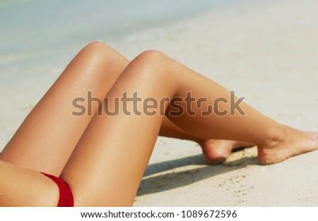 Women's beautiful sexy legs on the beach #1089672596