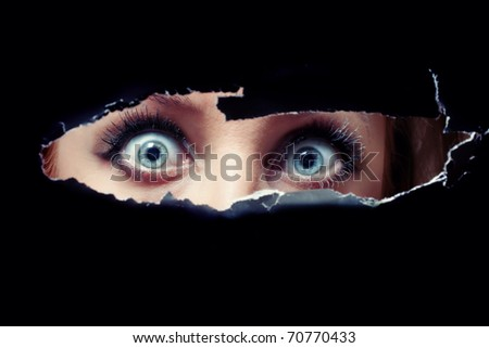 Women's blue eyes spying through a hole