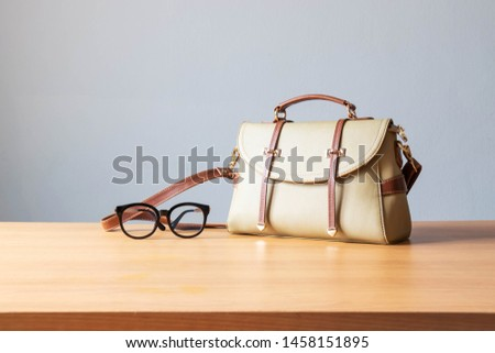Women's casual outfits accessories with handbag on table over gray background