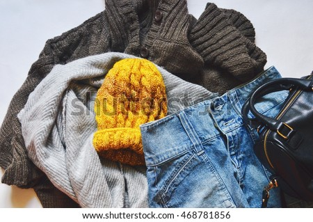 Women\'s clothes: a brown woolen cardigan, gray scarf, denim skirt and a yellow hat. Casual style. Autumn or winter outfit. Flat lay, top view photography