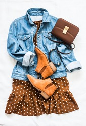 Women's clothing for spring, summer, autumn - denim jacket oversize, polka dot dress, suede chelsea boots and cross body bag on a light background, top view
