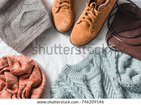 Women's clothing set - skirt, suede boots, sweater, scarf, leather cross body bag on a light background, top view. Winter, fall female clothing