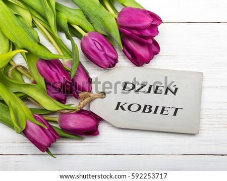 Women's day card with Polish words DZIE? KOBIET. Tulip flowers on white wooden background. Zdjęcia stock ©