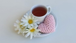 Women's Day, Mother's Day, Valentine's Day, Anniversary and Wedding Anniversary. Cup with tea, flowers and a crochet heart. White background. Space for text.