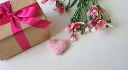 Women's Day, Mother's Day, Valentine's Day, Anniversary and Wedding Anniversary. Flowers, a crochet heart and a beautiful gift wrapped in a pink ribbon. Wood background. White base. Space for text.