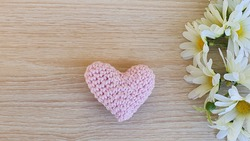 Women's Day, Mother's Day, Valentine's Day, Grandparents day. Anniversary and Wedding Anniversary. Flowers and a crochet heart. Wood background. Space for text.