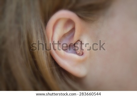Women\'s ear with a hearing aid