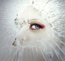 Women's eye through the broken glass