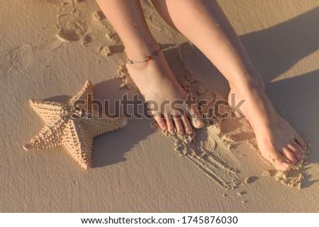 Women's feet and starfish on yellow sand. Stock fotó ©
