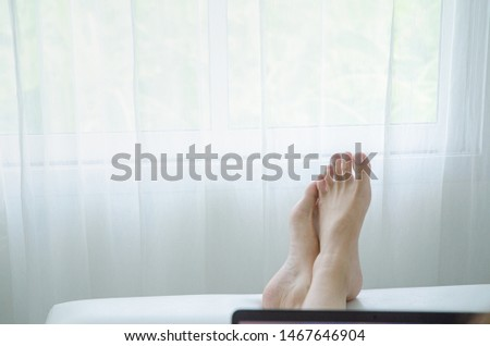 Women's feet are placed on the sofa in the bedroom. Relaxing concept on a relaxing day.Do not focus on the main object of this image. #1467646904