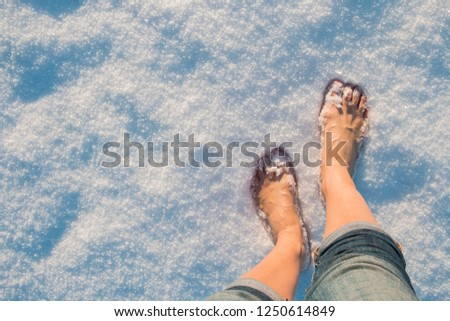 A girl goes barefoot to white cold snow, hardening Images