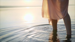 Women's feet go to the water on the stones. Girl goes barefoot on the stones of a mountain river. Girl's feet in water