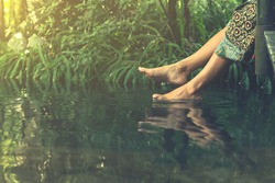 Women's feet in the water plunges feeling freshness