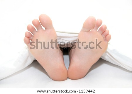 Women's feet poking out of the end of the bed