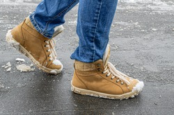 Women's foots in jeans and demi-season suede boots on asphalt with snow and reagents. Use of reagents when cleaning city streets from snow, damage to suede and leather shoes.