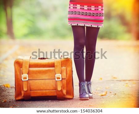 Women's foots near suitcase at autumn outdoor.