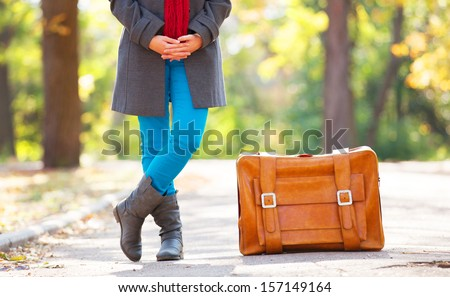 women's foots near suitcase at...