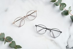 Women's glasses and eucalyptus leaves on marble table top view.