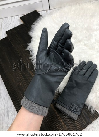 Women's gray leather gloves on a hand on a wooden background Stock photo ©
