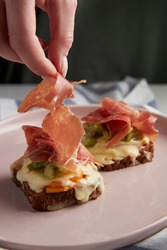 women's hand decorates Parma ham with toast or bruskets with cheese, zucchini and tomatoes. Useful food with meat and cereal bread. Healthy food in a pink plate. High quality photo