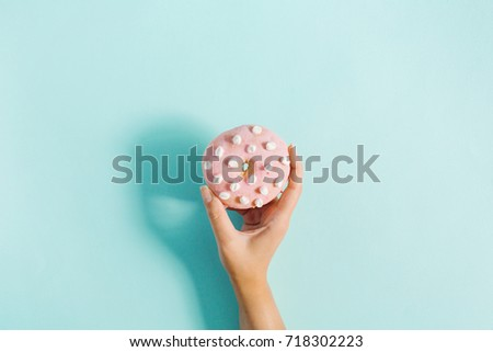 Women's hand holding donut on blue background. Minimal flat lay, top view concept